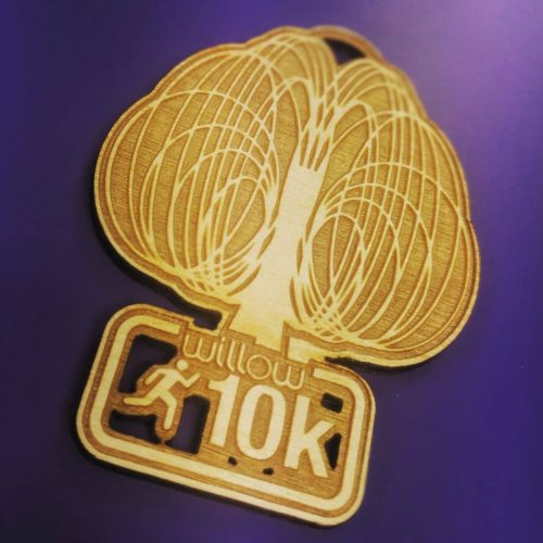wooden medals. Intricate laser cut wooden medals manufactured in the UK. Purple background warm wooden medal. Willow 10K sports medals 2020.