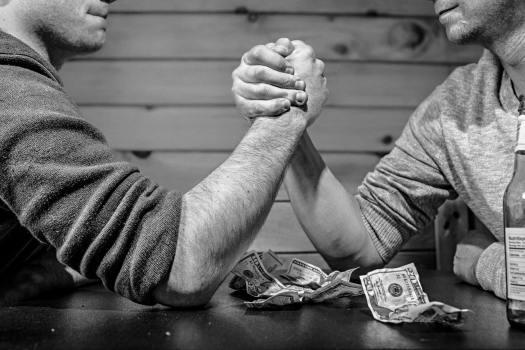 people arm wrestling - renting vs buying