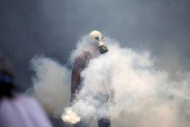 A demonstrator holds a tear gas canister during clashes with riot police in Caracas, Venezuela, on April 19, 2017. (Photo: Carlos Garcia Rawlins / Reuters)
