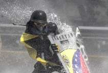 An opposition demonstrator is hit by the jet from a riot police water cannon during a protest against President Nicolas Maduro in Caracas, on May 10, 2017. (Photo: Juan Barreto / AFP / Getty)