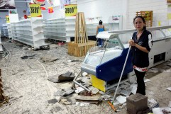 Workers clean the floor next to empty shelves and refrigerators in a supermarket after it was looted in San Cristobal, Venezuela, on May 17, 2017. (Photo: Carlos Eduardo Ramirez / Reuters)