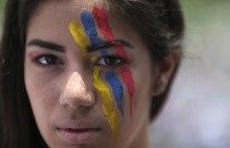 A woman with her face painted in the colors of Venezuela's national flag takes part in the blockade of a highway in Caracas on April 24, 2017. (Photo: Fernando Llano / AP)
