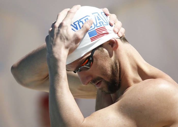 Apr 16, 2015; Mesa, AZ, USA; Michael Phelps adjusts his cap before swimming in the Men's 100 meter butterfly prelims during the 2015 Arena Pro Swim Series at the Skyline Aquatic Center. Mandatory Credit: Rob Schumacher/Arizona Republic via USA TODAY Sports