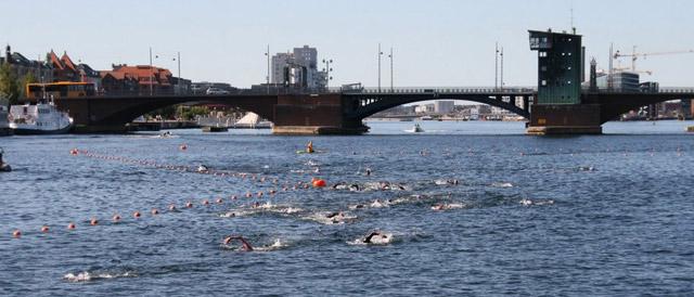 Udsigt over kanalen med svømmere. Langebro i baggrunden
