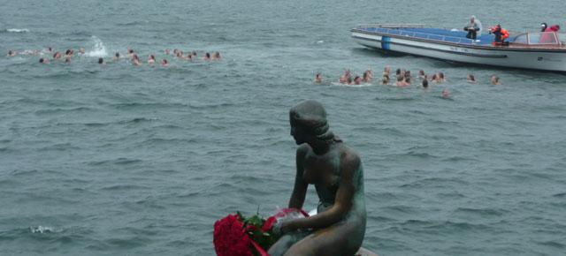 Den lille Havfrue med roser og 95 hvinende, frysende piger, der forsøger at lave tallet 95 i vandet bag hende