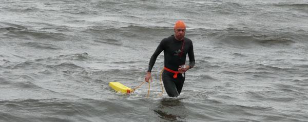 Mand i sort våddragt, der går i land med svømmetorpedo spændt om maven