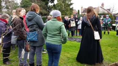 people stood in a garden singing