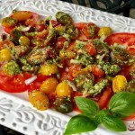 Pesto Tomato Salad is an easy 4 ingredient recipe. Garden fresh tomatoes and red onion are tossed in a homemade pesto transforming juicy tomatoes into a recipe that's bursting with fresh flavor and summertime goodness. #salad #tomato #tomatosalad #pesto #threeingredientrecipe #easyrecipe #summer #farmersmarket #heirloomtomatoes #vineripenedtomatoes #sidedish #swirlsofflavor