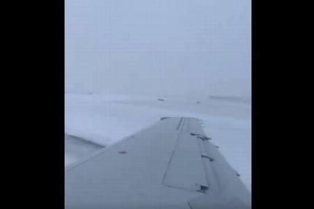 雪のため空港で旅客機がスリップ、滑走路からそれていく様子を機内で撮影