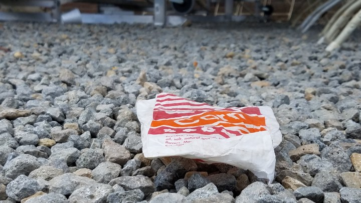Colourful popcorn wrapper lays on the ground.