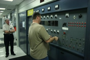 Technician presetting the tuning controls of a GE 250 kW transmitter for the next operating frequency (Click to enlarge)