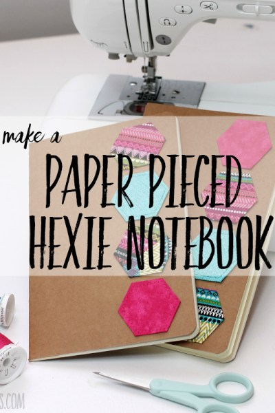 notebook decorated with fabric scraps sewn into the shape of a hexagon with english paper piecing