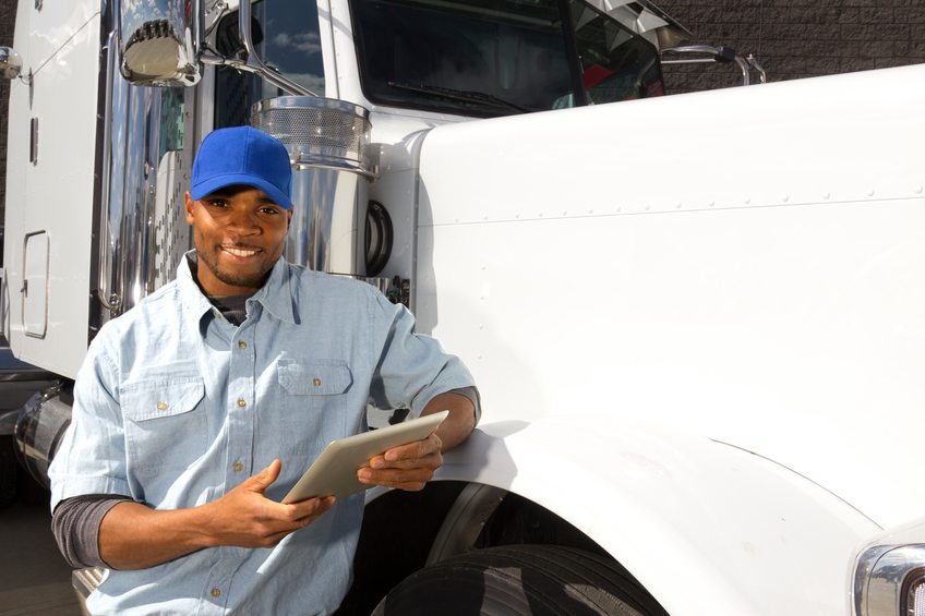 An image from the transportation industry of a truck driver leaning against his truck using a tablet PC.