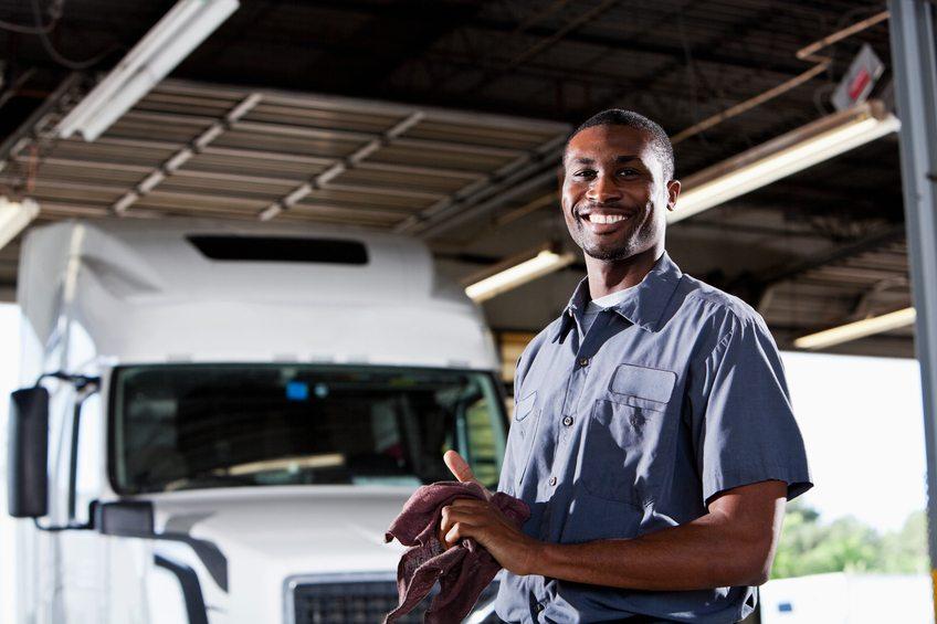 African American man (20s) in service garage repairing semi-truck.