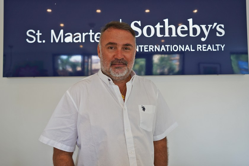 Man stands in front of St Maarten sotheby's realty sign in office setting