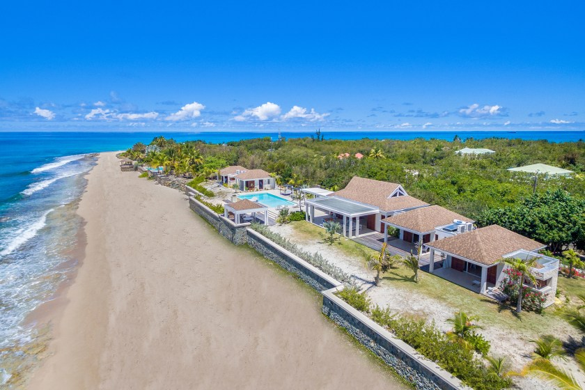 drone photos with a beach on the left and villa turtle nest on the right with pool