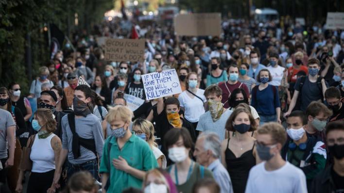 رفع حوالي 5000 شخص، وهم يضعون الكمامات تماشياً مع قواعد مكافحة انتشار فيروس كورونا، لافتات عليها شعارات مثل