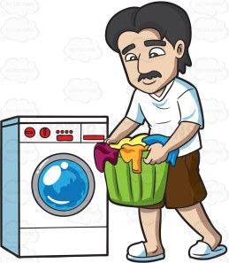 A man with black hair and mustache, wearing a white shirt and slippers, brown shorts, carries a green laundry basket full of clothes, that he will place inside the white washing machine