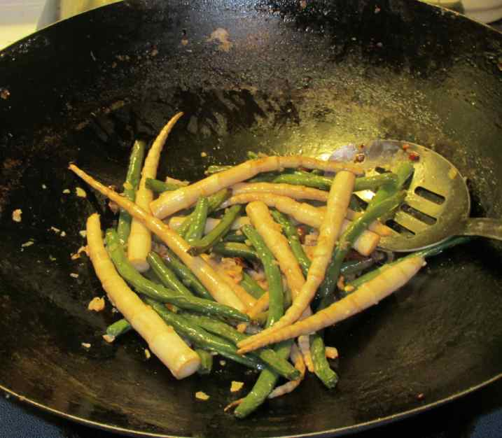 Stir-frying pre-fried green beans and bamboo shoots with aromatic seasonings