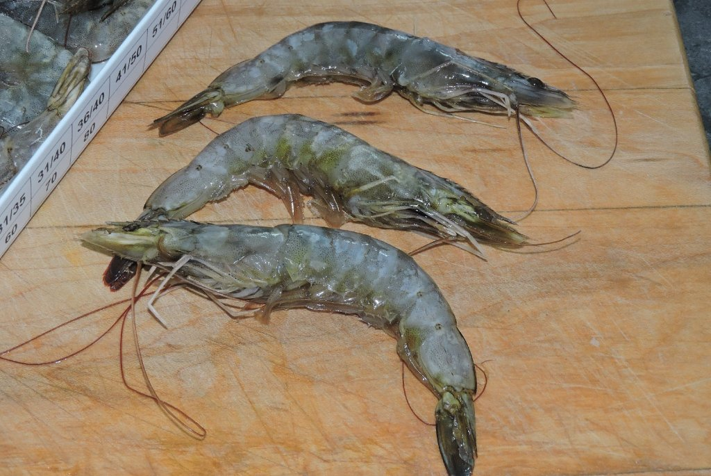 Unpeeled raw shrimp with heads still attached.