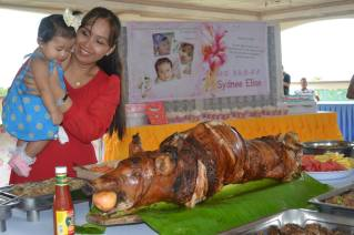 Sydnee's first glimpse and taste of a roasted pig!