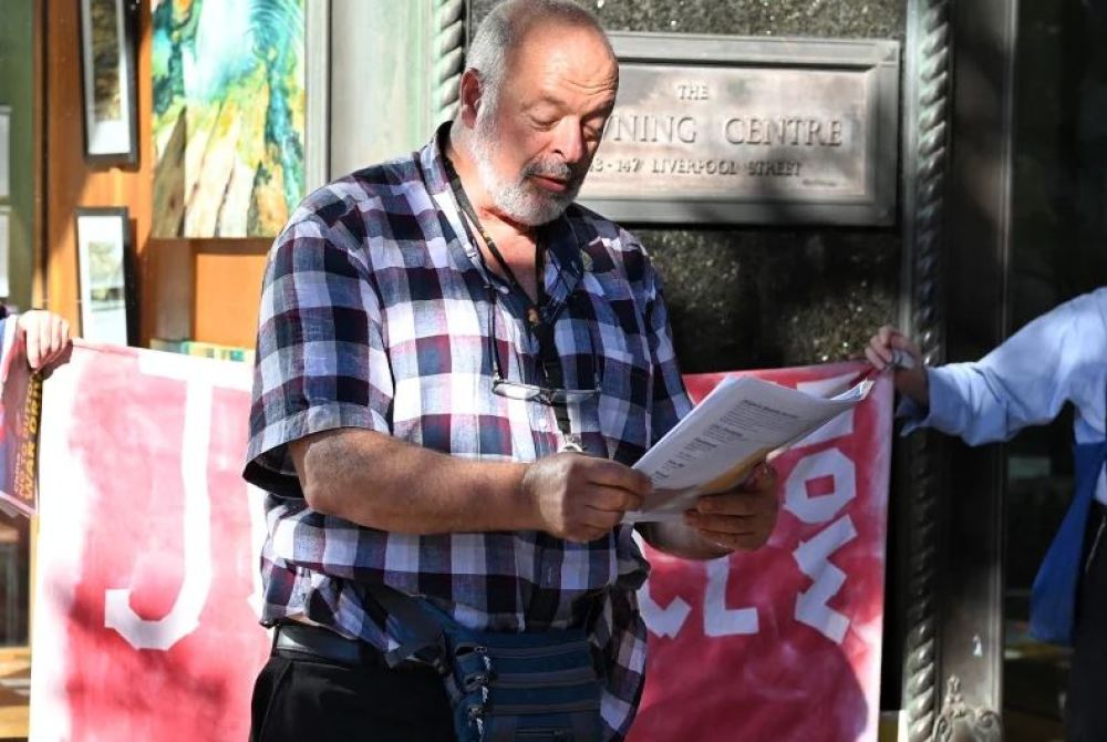 Activist Stephen Langford reads poetry outside the Downing Centre court.