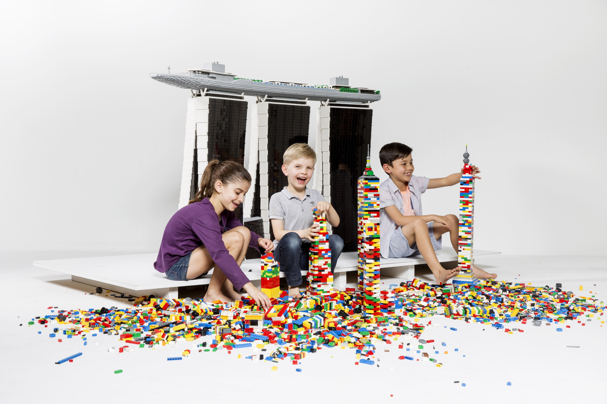 Kids playing with LEGO in front of a large scale LEGO Marina Bay     Lego