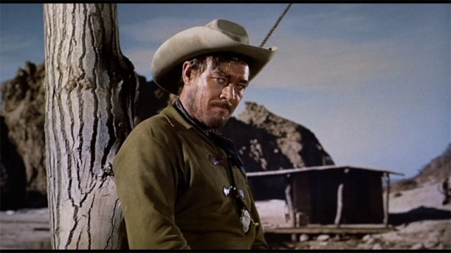 Bob Amory on the Edge - Man with cowboy hat leans on a tree with a basic hut in the background