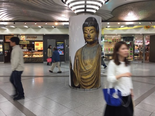 Buddha sculpture exhibit ad at Osaka Station City.