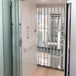 Symmetry Home Elevator with painted white interior, glass door and clear acrylic accordion gate.