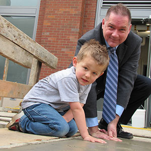 Hallie Ford Center Director Rick Settersten helps a child make a hand imprint outside the Hallie Ford Center during its grand opening festivities.