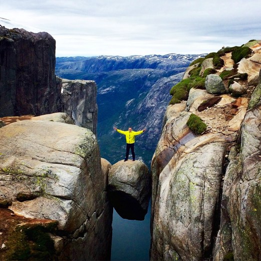 A man standing on Kjeragbolten, Rogaland, Norway © Scoundrelgeo with CCLicense