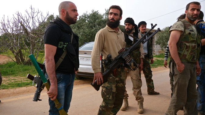 Rebel fighters wait for orders before proceeding to engage regime forces in Fou'a, Idlib Province.