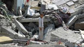 A boy stands in the rubble of buildings destroyed during Saudi airstrikes in the Yemen