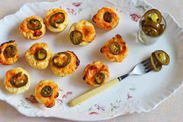 Spicy Pimento Cheese Biscuit Bites. Small biscuit cups filled with pimento cheese , topped with a pickled jalapeno slice and baked.