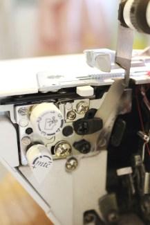 på Bernina 1150 eller modeller som har mtc-knapp løsnes skruen under den hvite rullesømsknappen for å montere snorguiden