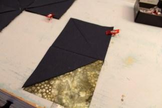 Legg neste foldede trekant på plass - bruk gjerne klemmer i stedet for nåler