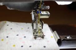 Legg falden med retten opp og sjekk at sømmen sys presis over overlockkanten på baksiden
