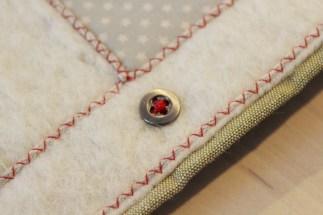 Flott finnish og dekor med rød sikksakk over garnet. Knappen er også sydd i med rød tråd. Som en liten ekstra detalje har jeg sydd ett kryss i midten av knappen i stedet for paralelle sømmer.