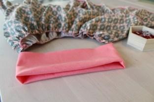 Fold ribben dobbelt og sy sammen på kortsiden dvs de 16cm så du får en tube. Vreng tuben og fold den dobbel så sømmen ligger inne i linningen