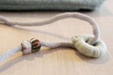 Gummiringen er dekket med Cotton Tube garnet og har fått en fin perle som prikken over i'en
