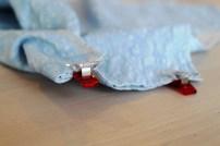 Legg forstykket og bakstykket rette mot rette. Fold forstykket rundt bakstykket - det er den delen som var bredere enn bakstykket. Sett en stoffklemme for å forhindre at stykkene forskyver seg.