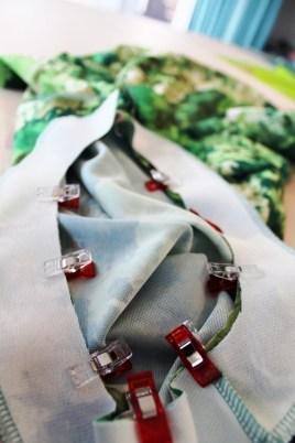 Bruk stoffklemmer for å feste belegget rette mot rette med kjolen. Start med den delen der skuldersømmen er sydd og legg overlocksømmene til hver sin side