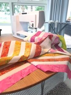Jeg valgte å sy min quilttopp noe mindre enn Suzy's mønster - dels fordi at jeg ikke ville blande fargene på batikkstoffene fordi jeg kun hadde 2 strimler av hverf farge og dels fordi dette skulle bli en babyquilt som ikke skulle bli så stor