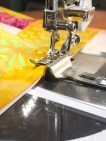 Strimlene fra jellyrollen måler 2 1/2 inch. Sømmonnet på en 1/4-inch sys uten problemer ved hjelp av guiden som er montert på sammen med foten