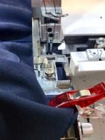 Skyv stoffet vekk fra knivene mens du syr - nålstopp nede forhindrer at stoffet sklir ut av overlocken
