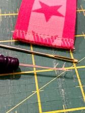 Fest trådkjedene inne i sømmen med en stoppenål. Om strikken er smal finnes det et smart verktøy fra Prym som drar trådkjeden med
