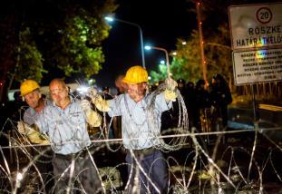 Röszke, 2015. szeptember 16. Az ideiglenes biztonsági határzárat erõsítik meg a lezárt Röszke 2 határátkelõhelyen 2015. szeptember 16-án. Korábban a magyar rendõrök könnygázt és vízágyút is bevetettek a határ magyar oldaláról az õket Szerbia felõl dobáló és a határzárat megrongáló illegális bevándorlókkal szemben. Ekkor sérült meg a határzár. MTI Fotó: Mohai Balázs