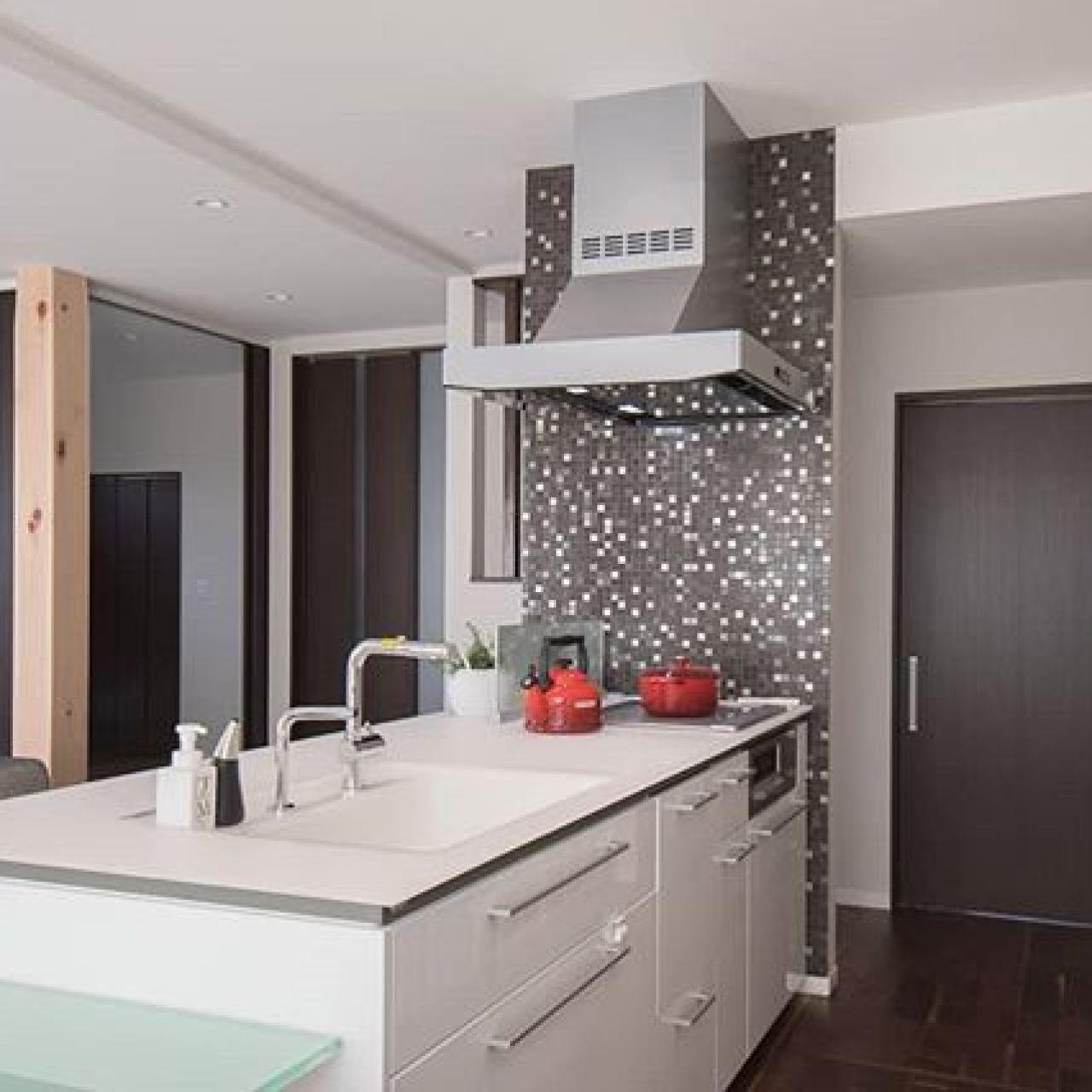 アイランドキッチンを中心に、右奥のドアから洗面脱衣室へ、左奥のドアから玄関ホールへ、玄関ホールから洗面脱衣室へつながる回遊型の導線。家事にはベストなプランです。#TOTO,#Crasso,#アイランドキッチン,#モザイクタイル,#エコカラット,#30帖大,#高い天井好き