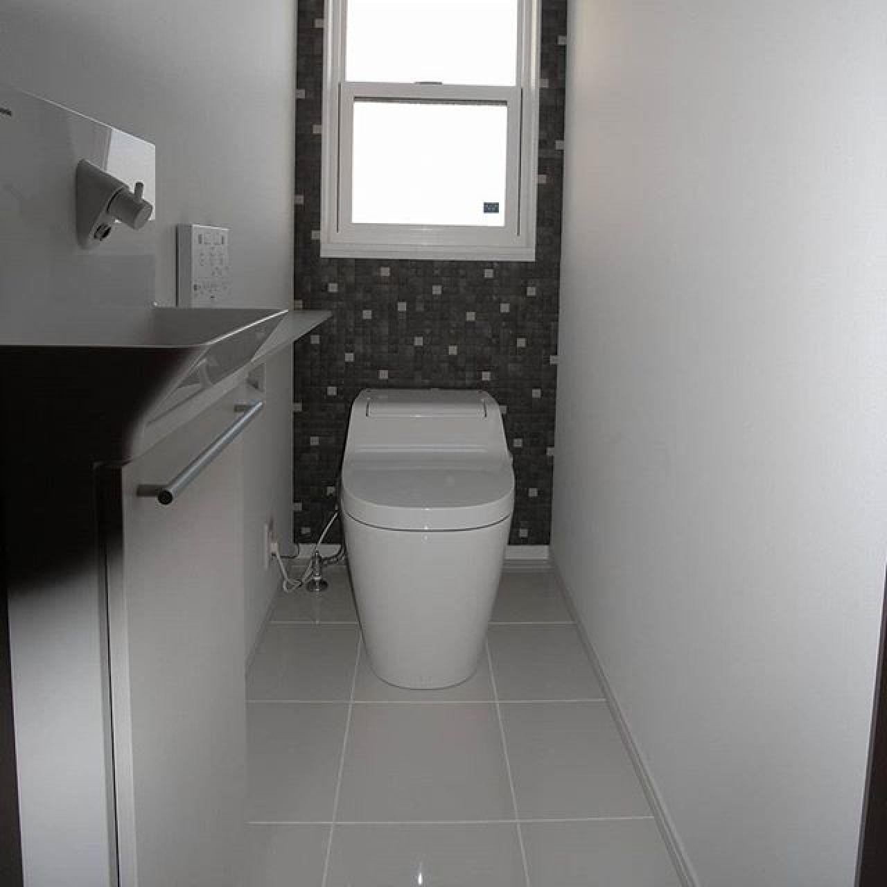 クッションフロアーとすることが多いトイレの床。白いタイル床に奥の壁はエコカラットタイル。床暖房だと蓄熱効果でじんわり暖かい。#トイレ #アラウーノ #タイル床 #エコカラット #手洗い #注文住宅 #上げ下げ窓 #APW330